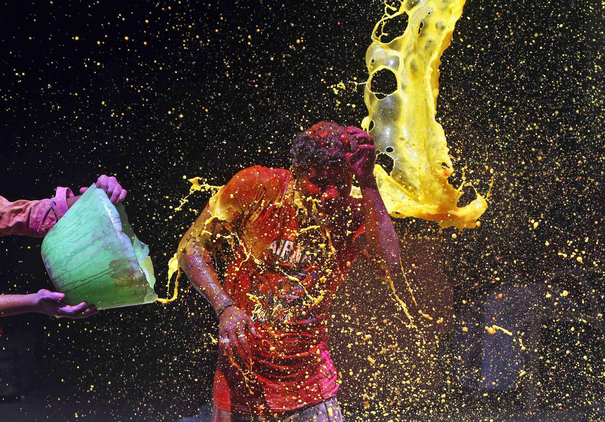 A man reacts to coloured water being splashed over him during Holi celebrations in the southern Indian city of Chennai March 17, 2014. Holi, also known as the Festival of Colours, heralds the beginning of spring and is celebrated all over India. REUTERS/Babu (INDIA - Tags: SOCIETY RELIGION TPX IMAGES OF THE DAY) ORG XMIT: DEL01